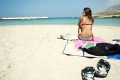 Mujer joven que se sienta en una playa hermosa Imagen de archivo