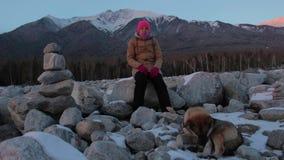 Mujer joven que se sienta en una roca en el pie de las montañas con su perro almacen de video