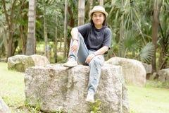 Mujer joven que se sienta en una roca grande Imagen de archivo