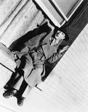 Mujer joven que se sienta en una ropa de los hombres que llevan del travesaño de la ventana (todas las personas representadas no  Imagen de archivo libre de regalías