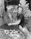 Mujer joven que se sienta en una sala de estar que abraza un presente el día de la Navidad (todas las personas representadas no s Foto de archivo libre de regalías