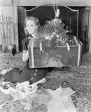 Mujer joven que se sienta en una sala de estar que muestra un presente (todas las personas representadas no son vivas más largo y Fotografía de archivo libre de regalías