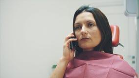 Mujer joven que se sienta en una silla dental para el nombramiento de un doctor Durante este tiempo, ella era muy preocupante sob almacen de video