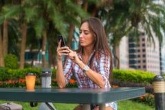 Mujer joven que se sienta en una tabla al aire libre usando su teléfono móvil Mensajes de texto femeninos de la lectura en smartp Foto de archivo libre de regalías