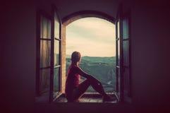 Mujer joven que se sienta en una ventana vieja abierta que mira en el paisaje de Toscana, Italia Imágenes de archivo libres de regalías