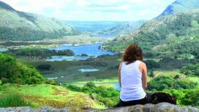 Mujer joven que se sienta encima de una montaña almacen de video