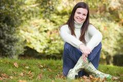 Mujer joven que se sienta entre árboles Foto de archivo libre de regalías