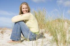 Mujer joven que se sienta entre las dunas Imagen de archivo