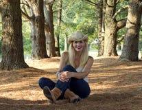 Mujer joven que se sienta entre los árboles fotografía de archivo