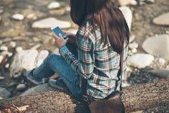 Mujer joven que se sienta a lo largo del río y de mandar un SMS Fotos de archivo libres de regalías