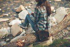 Mujer joven que se sienta a lo largo del río y de mandar un SMS Fotos de archivo