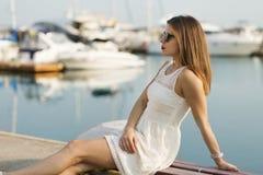 Mujer joven que se sienta por el puerto deportivo Imagen de archivo libre de regalías