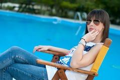 Mujer joven que se sienta por la piscina Foto de archivo libre de regalías