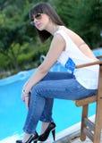 Mujer joven que se sienta por la piscina Fotos de archivo