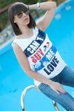 Mujer joven que se sienta por la piscina Imágenes de archivo libres de regalías