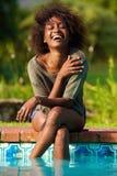 Mujer joven que se sienta por la piscina con los pies en agua Fotografía de archivo libre de regalías