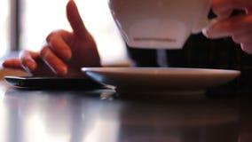 Mujer joven que se sienta por la ventana en un café usando smartphone y el café de consumición almacen de video