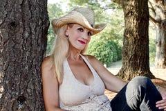Mujer joven que se sienta por los árboles fotografía de archivo libre de regalías