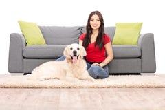 Mujer joven que se sienta por un sofá con su perro Fotos de archivo libres de regalías
