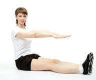 Mujer joven que se sienta que hace ejercicios del deporte Fotografía de archivo libre de regalías