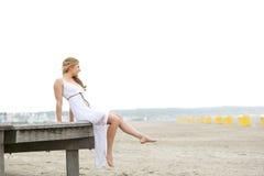 Mujer joven que se sienta solamente en la playa foto de archivo libre de regalías