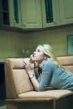 Mujer joven que se sienta solamente y que habla en el teléfono Fotografía de archivo