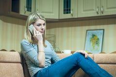 Mujer joven que se sienta solamente y que habla en el teléfono Imágenes de archivo libres de regalías