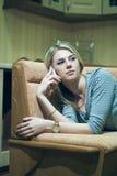Mujer joven que se sienta solamente y que habla en el teléfono Fotos de archivo