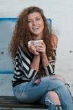 Mujer joven que se sienta sosteniendo una taza de café Fotos de archivo