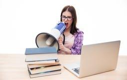 Mujer joven que se sienta y que grita en megáfono Foto de archivo libre de regalías