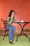Mujer joven que se sienta y que habla en el teléfono celular Imagenes de archivo