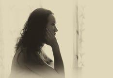 Mujer joven que se sienta y que piensa cerca de luz brillante de la ventana imagen filtrada blanco y negro Imágenes de archivo libres de regalías