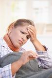 Mujer joven que se siente mal tomando su temperatura Foto de archivo libre de regalías