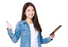 Mujer joven que se sostiene con la tableta y el pulgar para arriba Imagenes de archivo