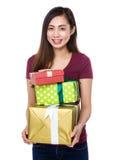 Mujer joven que se sostiene con las porciones de giftbox Foto de archivo