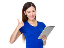 Mujer joven que se sostiene con PC y el pulgar de la tableta para arriba Imagenes de archivo