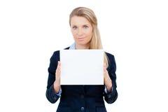 Mujer joven que se sostiene en la tarjeta en blanco en su mano Fotos de archivo