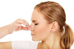 Mujer joven que se sostiene la nariz debido a un mún olor foto de archivo libre de regalías