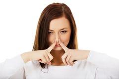 Mujer joven que se sostiene la nariz debido a un mún olor imagen de archivo