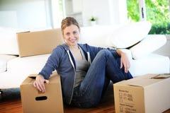 Mujer joven que se traslada al nuevo apartamento imagen de archivo