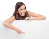 Mujer joven que señala en el cartel en blanco Fotos de archivo