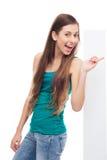 Mujer joven que señala en el cartel en blanco Foto de archivo libre de regalías
