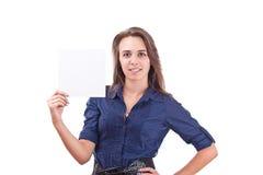 Mujer joven que señala en la tarjeta en blanco en su mano Foto de archivo libre de regalías