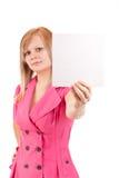 Mujer joven que señala en la tarjeta en blanco en su mano Imagen de archivo libre de regalías