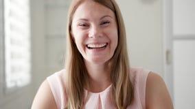 Mujer joven que sienta en casa hablar vía el mensajero app Skype Mano que agita sonriente en el saludo almacen de video