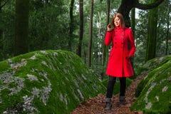 Mujer joven que siente caminar triste solamente en la trayectoria de bosque que lleva la capa larga roja imagen de archivo libre de regalías
