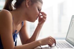 Mujer joven que siente cansada, dando masajes al puente de la nariz, sufriendo de Fotografía de archivo