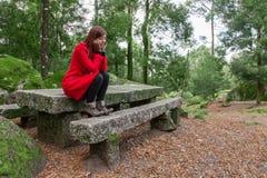 Mujer joven que siente la sentada presionada en un bosque Fotografía de archivo