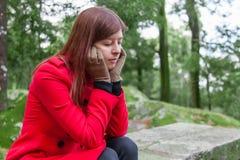 Mujer joven que siente la sentada presionada en un bosque Imagenes de archivo