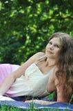 Mujer joven que soña despierto en parque Imagen de archivo